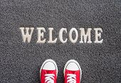 Welcome Carpet With Red Sneakers On It. poster