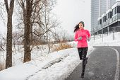 Winter running Asian girl wearing cold weather clothing for outside exercise in snow storm snowfall  poster