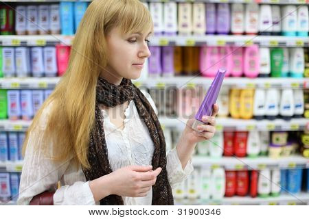 Blonde girl wearing white shirt chooses shampoo in large store; shallow depth of field