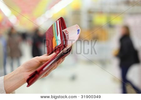 Woman hand keep red purse with money and credit cards in store; shallow depth of field