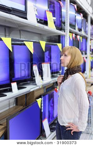 Blonde girl wearing scarf looks at plasma TVs in supermarket; shallow depth of field