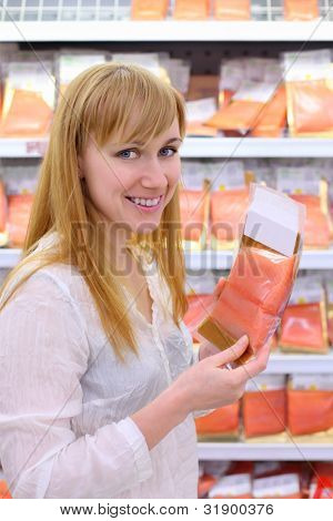 Happy girl wearing white shirt chooses salmon in store; shallow depth of field