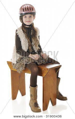 ein glücklich elementare Mädchen sitzen schön in ihrem Reiten Helm und Stiefel beim Spagat zwischen eine Bank wie