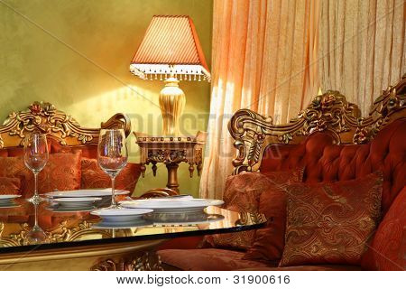 beautiful table with serving, lamp and carved sofa in eastern luxury restaurant