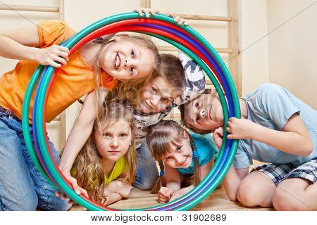 Portrait of laughing children looking through hula hoops