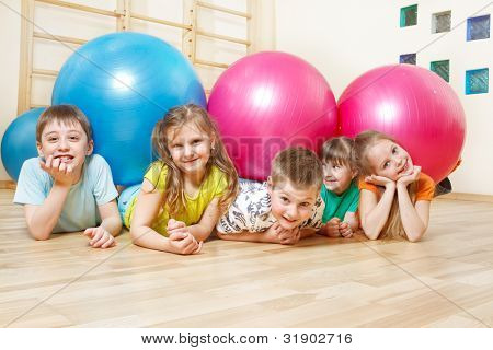 Five happy kids lie in gym with large balls
