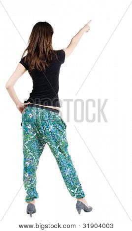 Back view of young brunette woman pointing at wall . beautiful fashion-monger girl  in fashionable clothing showing gesture. Rear view. Isolated over white background.