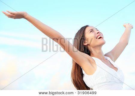 Conceito de liberdade de êxtase de felicidade. Mulher feliz sorrindo alegre com braços dança na praia no verão