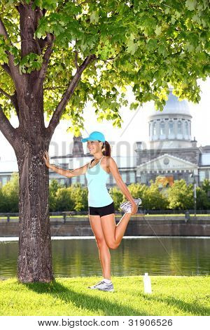 Woman runner in Montreal stretching after jogging workout outdoor on sunny summer day. Montreal Old Port, Montreal, Quebec, Canada. Multiracial Asian / Caucasian female sport fitness model.