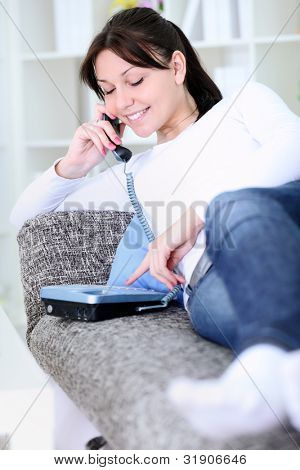 Pretty woman making phone call on couch in living room, smiling.