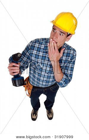 craftsman holding a drill and looking upset