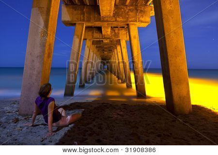 woman sitting under pier at night, time exposure.