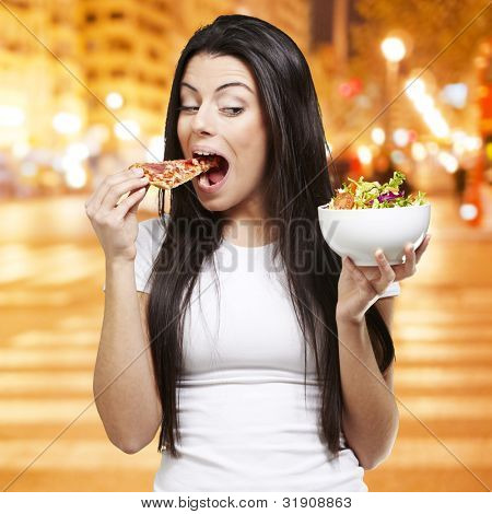 woman choosing a slice of pizza instead of a salad against a city night background