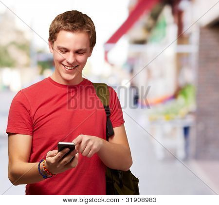 portrait of young man touching mobile screen at street