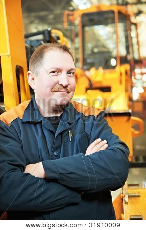 Portrait of adult experienced industrial worker over heavy industry machinery production line manufacturing workshop