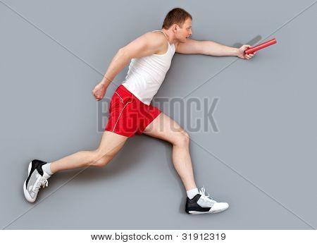 Sportive guy hurrying to pass the relay baton