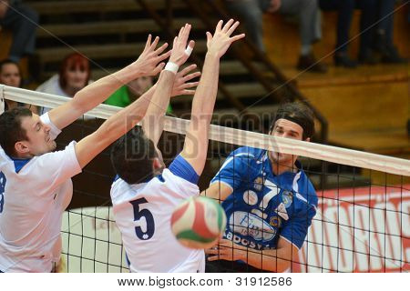 KAPOSVAR, HUNGARY - MARCH 17: Andras Geiger (R) in action at a Hungarian Championship volleyball game Kaposvar (blue) vs. Kazincbarcika (white), March 17, 2012 in Kaposvar, Hungary.