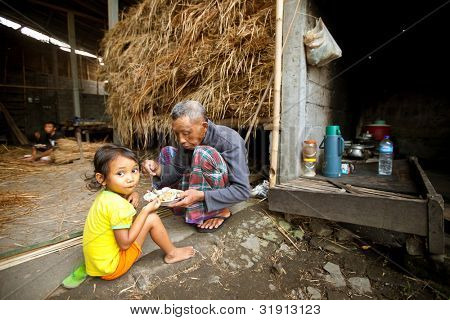 BALI - APRIL 3: Unidentified poor child eats with his father during a break working on the farm  on April 3, 2012 on Bali. Daily caloric intake per capita in Indonesia is 2891 kcal per person.