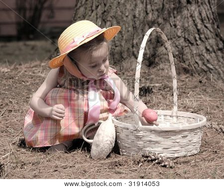 Little girl dressed in her sunday best on easter with a basket and an egg, this image was made to have an old feel to it. The clothes and egg are done in muted colors, the rest is in a light sepia