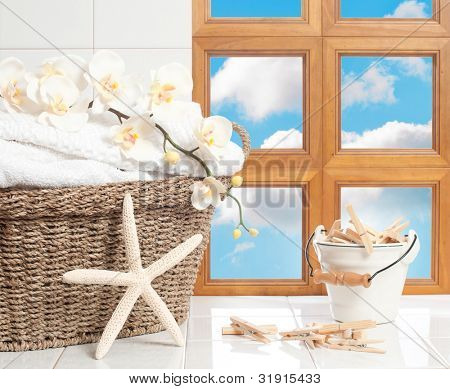 Basket of fresh laundry with clothespins against a blue sky window