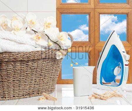 Housework concept with fresh laundry and iron against a window with blue sky
