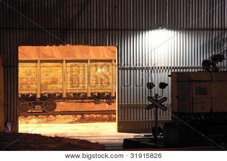 Gates of hangar at night and vagon inside