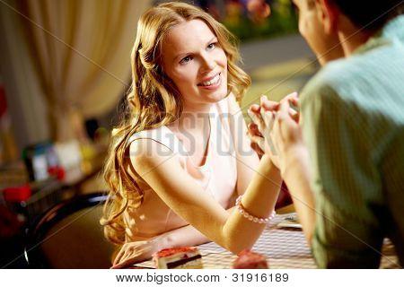 Una joven feliz sentado en el restaurante y mirando a su novio