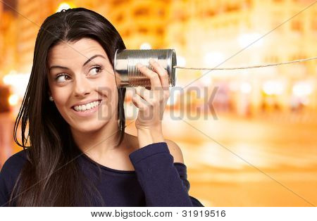 Young woman hearing using a metal tin can at night city