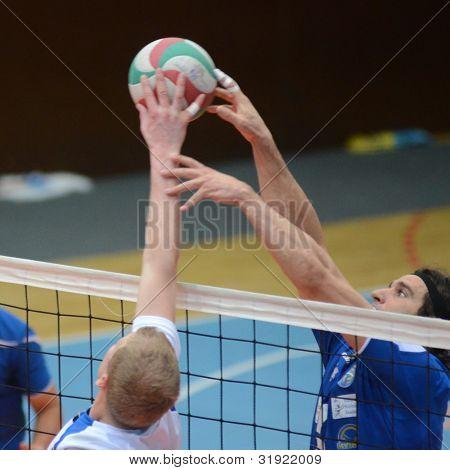 KAPOSVAR, HUNGARY - MARCH 17: Andras Geiger (in blue) in action at a Hungarian Championship volleyball game Kaposvar (blue) vs. Kazincbarcika (white), March 17, 2012 in Kaposvar, Hungary.