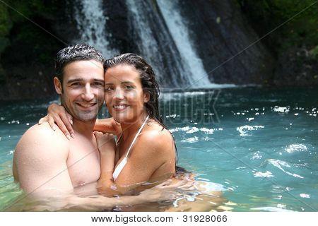 Feliz pareja bañarse junto a la cascada en la isla