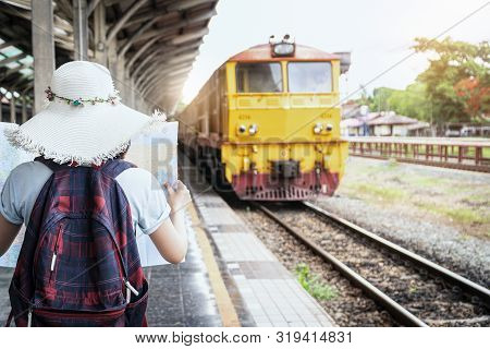 poster of Young Woman Traveler Holding Map Standing On Platform At Train Station For Travel. Travel Concept By