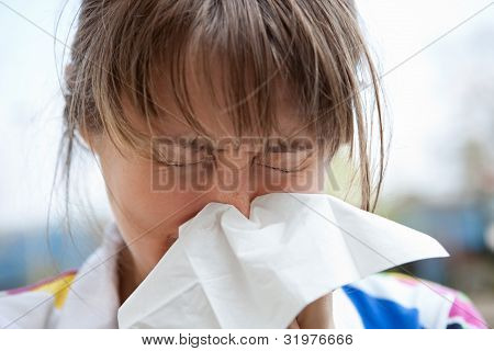 blonde female blowing her nose