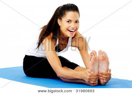 Athletic woman smiling while she stretches forward, Part of a collection of yoga poses by a fit active mixed race woman; sit-up pose.