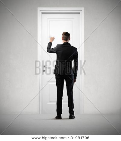 Businessman knocking at a door