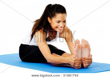 Athletic woman smiling while she stretches forward, Part of a collection of yoga poses by a fit active hispanic woman; sit-up pose