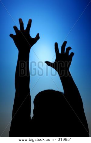 Picture or Photo of Silhouette of man reaching toward the sky. symbolic sign for upward mobility.