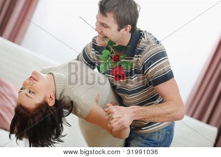 Romantic Young Couple Dancing With Red Rose At Home