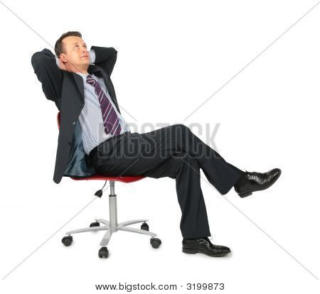 Dreaming Businessman Sits On Office Chair