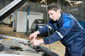 One young auto mechanic tighten screw with spanner during automobile car maintenance at engine repai