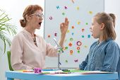Cute Blond Little Girl Opening Her Mouth During Speech Therapy With Senior Professional Therapist, C poster