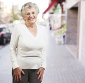 stock photo of beautiful senior woman  - pretty senior woman smiling against a street background - JPG