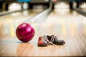 Pair of bowling shoes and ball in bowling alley poster