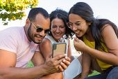 Group Of Excited Friends Watching Content On Phone Together. Man And Women Sitting On Grass In Park  poster