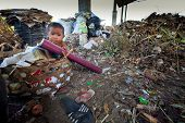 BALI, INDONESIA - APRIL 11: Unidentified child is sitting during his parents are working in a scaven