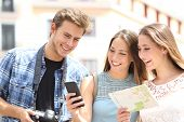 Three Happy Tourists Traveling Checking Smart Phone Gps And Map In The Street On Summer Vacation poster