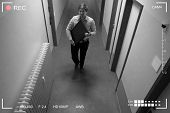 Young Man Stealing Computer Monitor Walking In Corridor Scene Through Cctv Camera poster