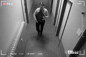 Young Man Stealing Computer Monitor Walking In Corridor Scene Through Cctv Camera poster