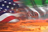 Usa United States Of America And Iran Relations / Iran Us War With Flags On Stormy Cloudy Orange Sky poster