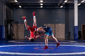 Two Young Men In Blue And Red Wrestling Tights Are Wrestlng And Making A Suplex Wrestling On A  Blue poster