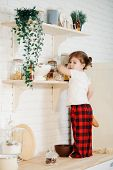 Cute Little Girl In Red Pajamas, Preparing Cookies In The Kitchen At Home. Sits On The Kitchen Table poster
